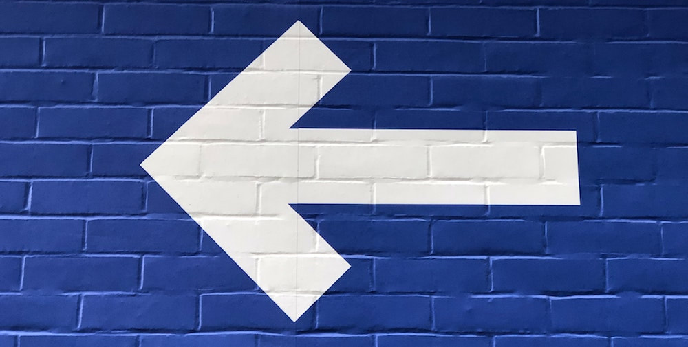 A white arrow pointing backwards on a blue brick wall.