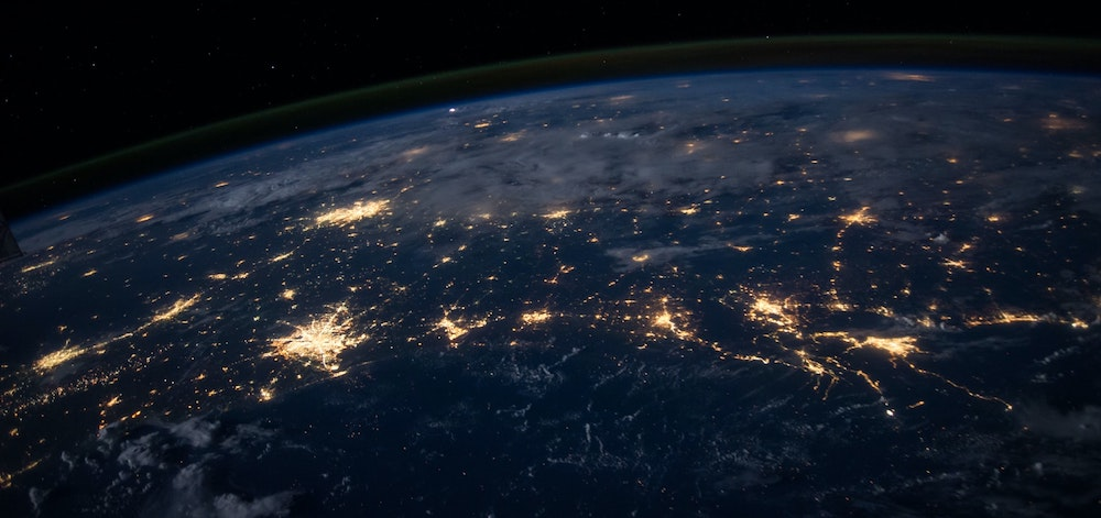 The Earth at night taken from space with major cities shining out of the darkness.