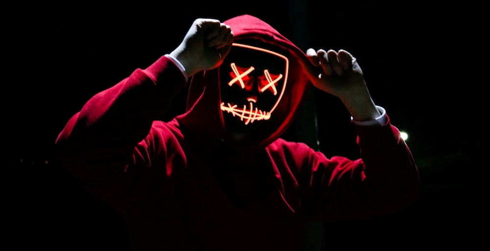 A person wearing a red hoodie with neon skeleton features across their face.