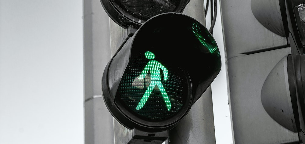 Close-up of the green man on a set of traffic lights.