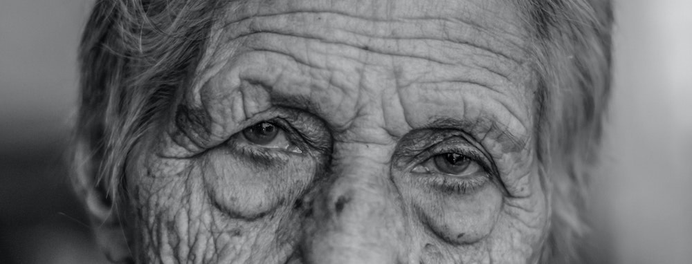 Close-up of an old woman's eyes and wrinkly forehead.