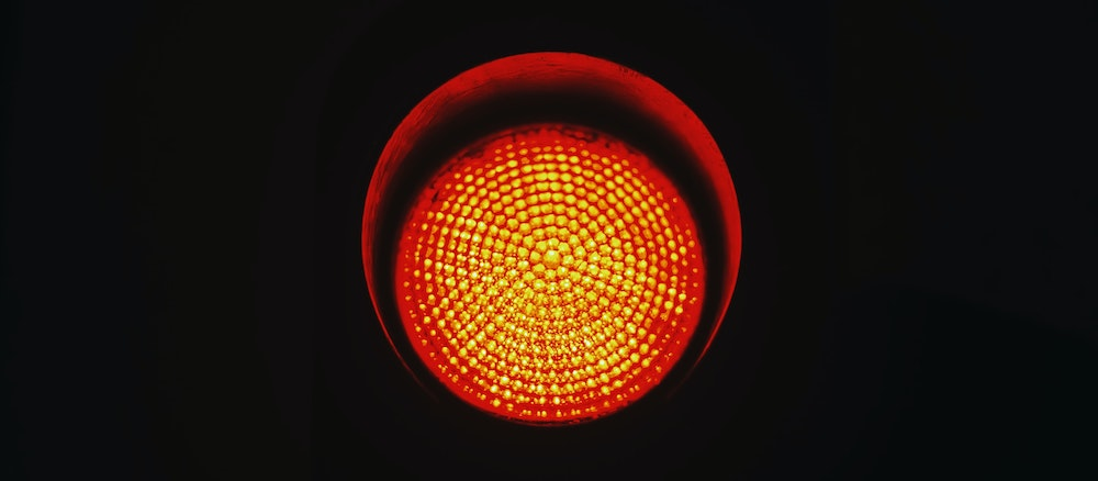 Close-up of a red traffic light with a black backdrop.